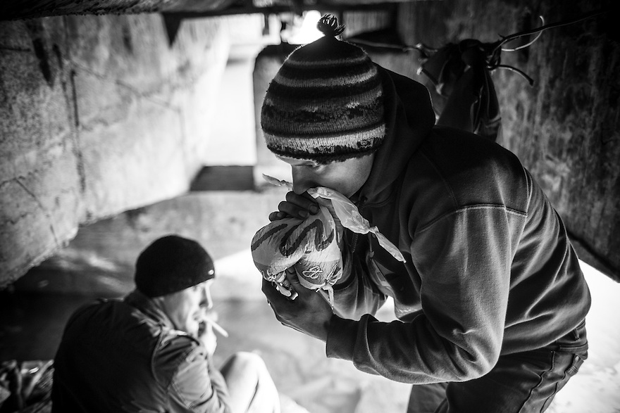 The crawl space under a bridge is home to three homeless men, two of whom are addicted to huffing paint in Bucharest.