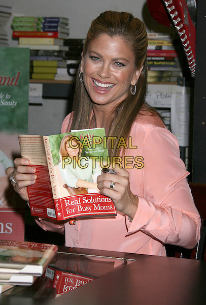 "KATHY IRELAND.Kathy Ireland Book Signing for ""Real Solutions for Busy Moms: Your Guide To Success And Sanity"" held at Book Soup, West Hollywood, California, USA..April 14th, 2009.half length pink orange coral blouse top sheer table.CAP/ADM/MJ.©Michael Jade/AdMedia/Capital Pictures."