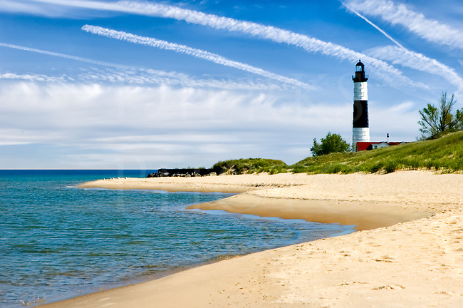 This scenic lighthouse sits along the eastern shore of Lake Michigan on the Great Lakes. It&rsquo;s known as Big Sable and sits close to Ludington, out in the sandy dunes north of town. Interestingly, you can&rsquo;t get there with a car: you can either walk up the beach for almost a mile as I did to to take this shot, or ride a bicycle on a trail across the dunes. Walking here forced me to slow down and be part of nature and this beautiful scene, letting it sink into my pores while enjoying every moment spent here. It was a small slice of momentary heaven and a great place to be.<br /> <br /> This was taken on a very calm and fair weather day with a fantastic sky and no surf at all...it&rsquo;s the wind that makes the waves on the big lakes and none were being pushed up onto the sand. You can easily visit here and other neighboring lighthouses and parks, and it&rsquo;s from Ludington that the large ferry goes across the expanse of Lake Michigan to the Wisconsin side. More information about this lighthouse and the area is at http://www.splka.org/