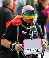A man in leather outfit carrying a for sale sign in this year's Pride Parade in the centre of Cardiff, Wales, UK. Sayurday 26 August 2017
