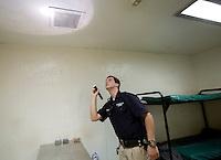 NWA Democrat-Gazette/JASON IVESTER <br /> Springdale Police Jailer Ryan Brown checks cells for contraband on Monday, Aug. 10, 2015, inside the Springdale jail.