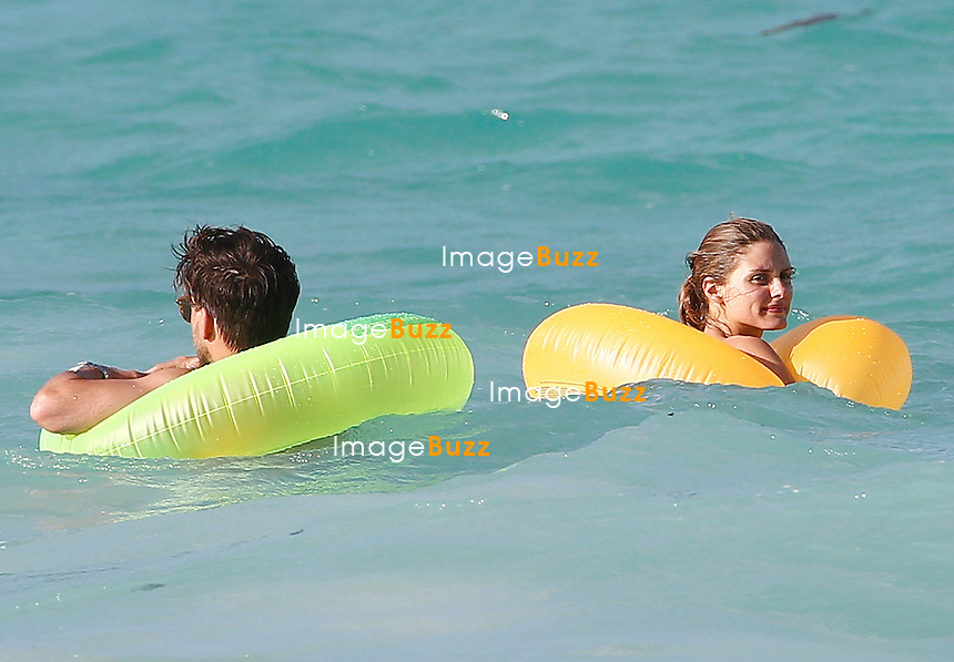 Olivia Palermo and Johannes Huebl play with rubber rings in the waves while enjoying their vacation in Saint Barths.<br /> January 10, 2014.