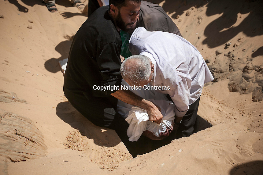 "August 20, 2014 - Gaza City, Gaza strip, Palestinian Territory: Palestinian men bury the body of the 9-months-old son of Mohammed Al-Daif (not pictured) after he was killed during a night raid airstrike in Sheik Redwan neighborhood of Gaza City as ""Protective Edge"" Israeli military operation resumed when the truce was broken in the Gaza strip. (Narciso Contreras/Polaris)"