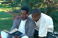 Grandfather age 70 and grandson age 13 reading.  St Paul  Minnesota USA