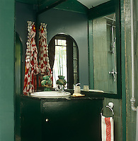 The wash basin and corner cabinet in the varnished green slate bathroom