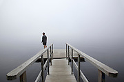 A man stands on the edge of a dock overlooking the Connecticut River in foggy conditions in Waterford, Vermont USA.