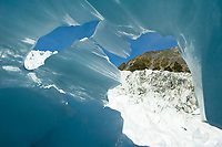 Looking out of textured blue ice cave toward  Main Icefall on Franz Josef Glacier, Westland Tai Poutini National Park, UNESCO World Heritage Area, West Coast, New Zealand, NZ