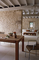 An old stone wall separates the living room from the kitchen-dining room