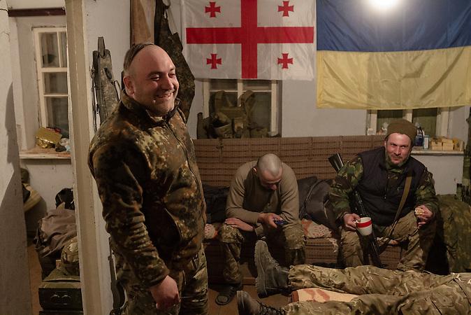 Die Soldaten sitzen am Abend zusammen. Im Hinitergrund hängt eine georgischen und ukrainische Flagge.