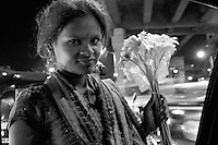 View from my car window Mumbai at night, a girl street vendor selling flowers to passing cars at a intersection, central Mumbai, India,