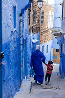 Chefchaouen, Morocco.  Mother and daughter Walking down a narrow Street.