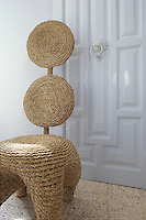 In the living room a contemporary chair made of woven straw is juxtaposed with an antique white-painted door
