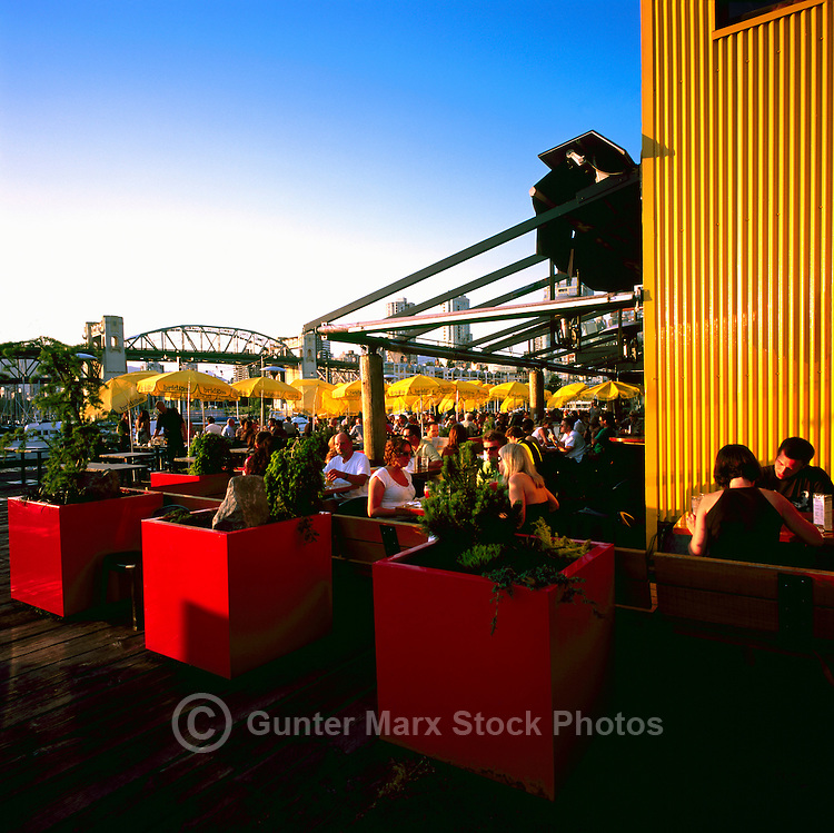 People dining outdoors at Bridges Restaurant on Granville Island, Vancouver, British Columbia, Canada, in Summer.  The Burrard Street Bridge is in the background.
