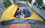 A family that fled violence in Herat, Afghanistan, eats breakfast in a tent in a city park in Belgrade, Serbia. The park has filled with refugees from Syria, Afghanistan and other countries stopping over on their way to western Europe.