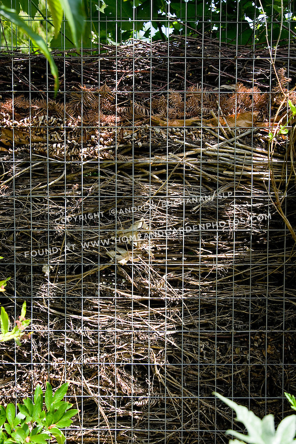 "A close up detail showing layers in a portion of a compost fence in a residential garden.  Made up of two layers of sturdy wire mesh screen held roughly 6-8"" apart, the home gardener places clippings and waste in the open top of the fence and allows them to fall to the bottom.  Subsequent layers build up in the fence, while the earlier clippings decompose and becomes usable compost to be removed from the bottom."