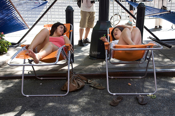 "New Yorkers relax in the shade while others ""dumpster dive"" in swimming pools made out of dumpsters on Park Avenue near Grand Central Station on 07 August 2010.  People were allowed 20-minute turns swimming in any of the three ""dumpster pools."""