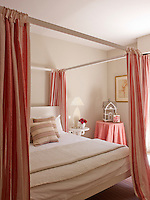 Red and white striped bed hangings create a warm and cosy feel to this guest room