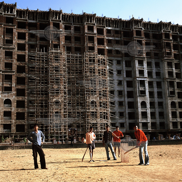 Construction workers and their sons, play cricket on a plot of land soon to be built on, in Borivli, Northern Mumbai. .