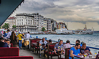 Urban Street Photography. <br /> Restaurant dining on the Galata bridge overlooking the Bosphorus Strait in Istanbul, Turkey. <br /> The dramatic lighting on the buildings and the birds flying overhead create the mood of this print. <br /> Everything seems in motion from the waves of the water, the birds flying, the people dining, and the cloud formations.