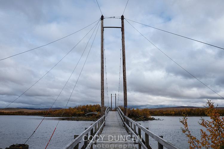 Wooden suspension bridge between islands on lake Tärnasjön, Kungsleden trail, Lapland, Sweden,