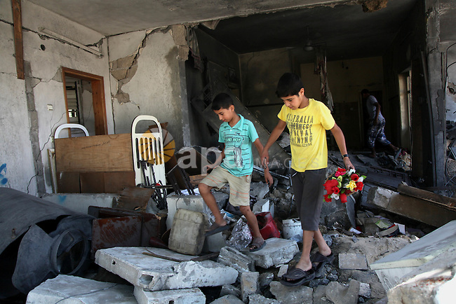 """Palestinian children inspect a damaged house was hit by an Israeli military strike in Gaza City on August 10, 2014. A senior Hamas official said there was a """"weak"""" possibility that Gaza truce talks would succeed and that Palestinian negotiators could leave Cairo after a meeting with Egyptian mediators. Photo by Ezz al-Zanoun"""