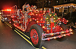 Antique fire engine in Cape May Christmas parade decorated with holiday lights