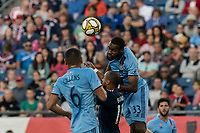 FOXBOROUGH, MA - SEPTEMBER 29: Sebastien Ibeagha #33 of New York City FC heads the ball away from Teal Bunbury #10 of New England Revolution during a game between New York City FC and New England Revolution at Gillette Stadium on September 29, 2019 in Foxborough, Massachusetts.