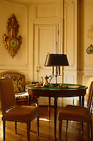 A pair of white lacquered Louis XVI Etruscan-style chairs stand next to a bouillotte table with a central lamp