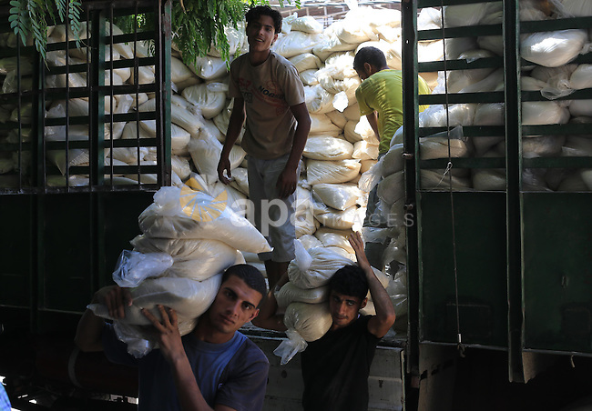 Palestinian men carry bags of rice at a distribution centre of the United Nations Relief and Works Agency (UNRWA) in Gaza City on August 11, 2014. An Israeli delegation arrived in Cairo for indirect negotiations with Palestinians on a durable truce in Gaza, Egypt and Israeli officials said. Photo by Mohammed Asad