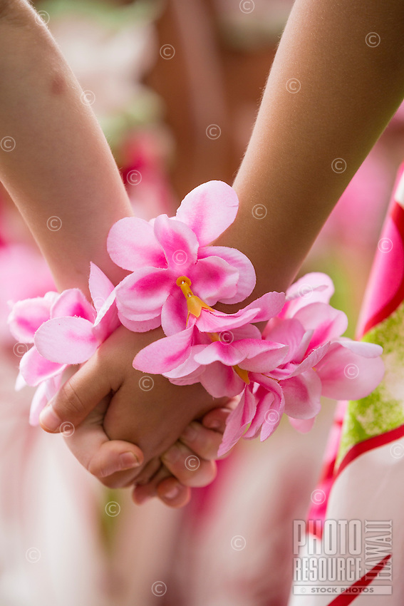 Two young girls wearing pink plumeria around their wrists hold hands before a keiki (or child) hula performance in Hale'iwa, O'ahu.