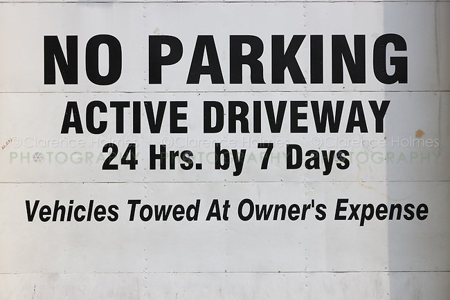 A No Parking sign on an active driveway garage door in New York City