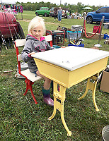 """Courtesy photo<br /> Quincy Morgan, granddaughter of Vicki and Darwin Smith, """"tries on"""" an old school desk for size at a recent swap meet."""