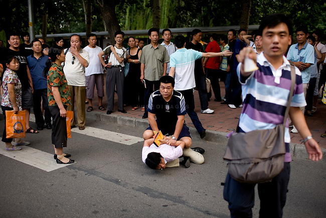 Secret police wrestle with a scalper during an arrest outside of Worker's Stadium in Beijing, China on Monday, August 18, 2008.  Kevin German
