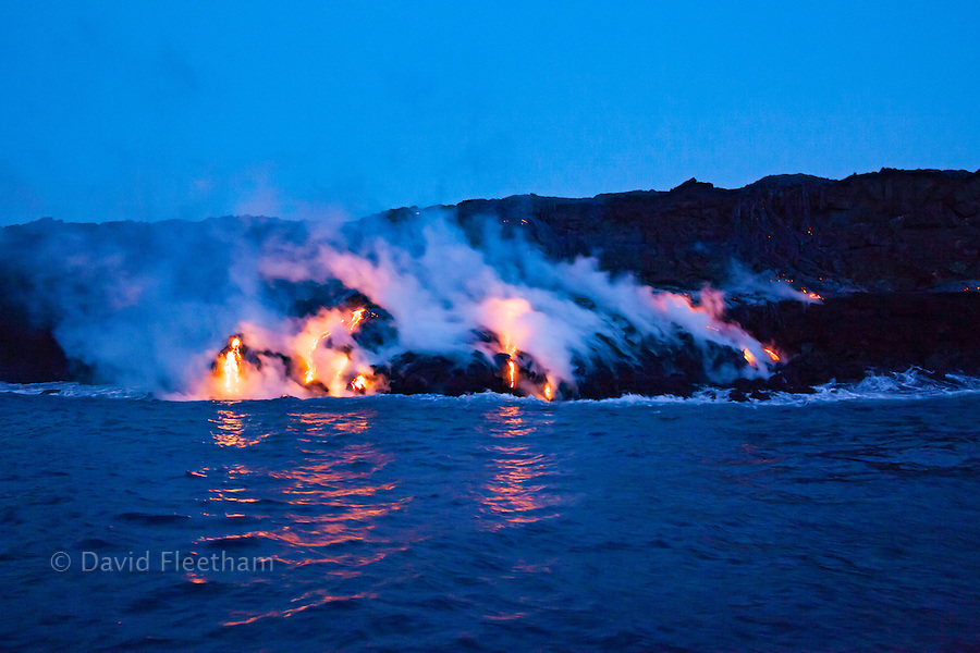 The Pahoehoe lava flowing from Kilauea has reached the Pacific Ocean near Kalapana, Big Island, Hawaii. This image was taken from a boat just before sunrise.