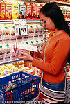 College student female shopping at supermarket, reading label on juice package