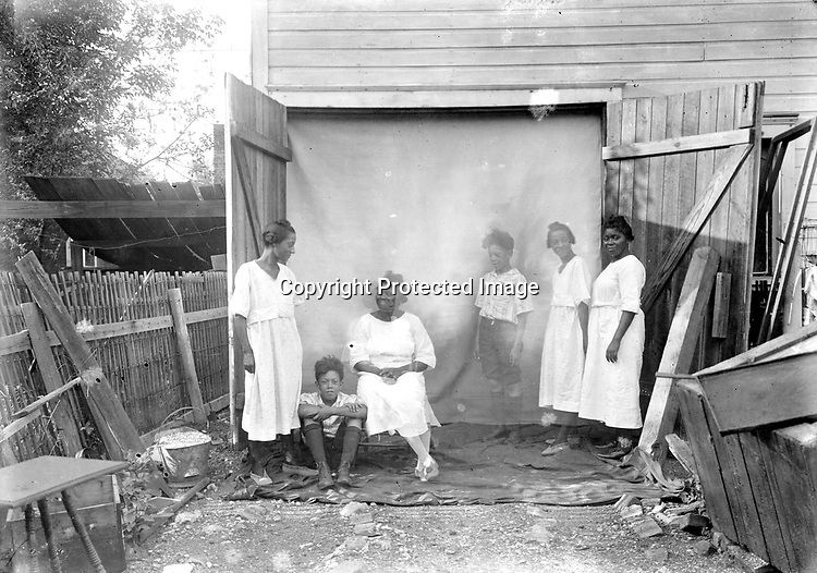 DOUBLE EXPOSURE<br /> Photographer John Johnson used the big double doors of an outbuilding-perhaps the frame barn he built in his back yard in 1908-to frame this image in which he tested his creativity and experimented with a double exposure. The six figures are three people photographed twice. His wife Odessa stands at right and sits in the center of the group.<br /> <br /> Photographs taken on black and white glass negatives by African American photographer(s) John Johnson and Earl McWilliams from 1910 to 1925 in Lincoln, Nebraska. Douglas Keister has 280 5x7 glass negatives taken by these photographers. Larger scans available on request.