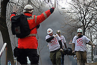 Red Cross Medics and volunteers lift  wounded protesters that fell on the field.  Kiev, Ukraine