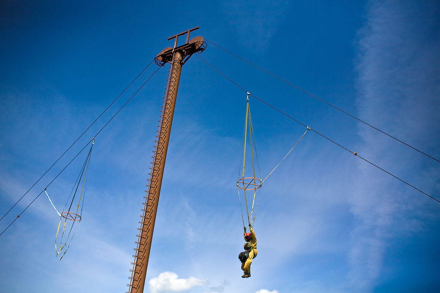 A smokejumper hangs from 'The Mutilator', a mechanized pulley system that lifts the trainee into the air and drops them approximately 35 feet to the ground at a maximum speed of 15 miles per hour.