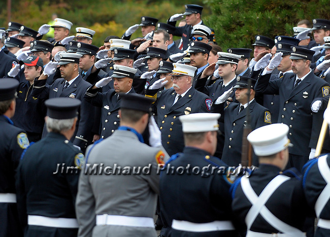 Firefighters salute as fire truck with the casket arrives, during the funeral for Hartford firefighter Kevin Bell, Monday, Oct 13, 2014, at the First Cathedral, in Bloomfield, Bell was killed in a house fire last week in Hartford. (AP Photo / Journal Inquirer, Jim Michaud)