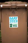 May 2019 date sticker on garden waste scheme brown compost collection bin, East Suffolk, England, UK