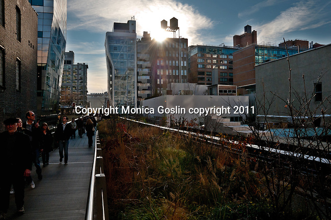 People walking on the Highline (public park on an old elevated train line) in New York City with views of the buildings and streets below on a sunny winter day