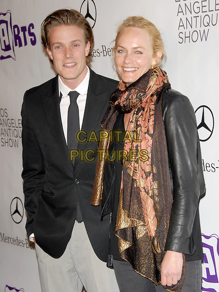 GUEST & AMBER VALLETTA .at the 15th Annual L.A. Antiques Show 2010 held at Barkar Hangar in Santa Monica, California, USA, .April 21st, 2010..half length brown orange gold black print scarf leather jacket suit jacket tie white shirt .CAP/RKE/DVS.©DVS/RockinExposures/Capital Pictures