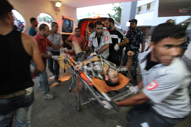 A wounded Palestinian protester arrives at al-Shifa hospital following clashes with Israeli security forces near the border fence between Israel and the Gaza Strip on October 9, 2015, in Gaza City. Tension and protests rose after an Israeli man on 09 October stabbed four Palestinians in southern Israel, in what is being seen as a revenge attack, officials said. On 08 October several violent incidents happened, including stabbings which left eight Israelis injured, one Palestinian was killed in East Jerusalem and six in the Gaza Strip in clashes with the army while at least six were injured on the West Bank. Photo by Ashraf Amra