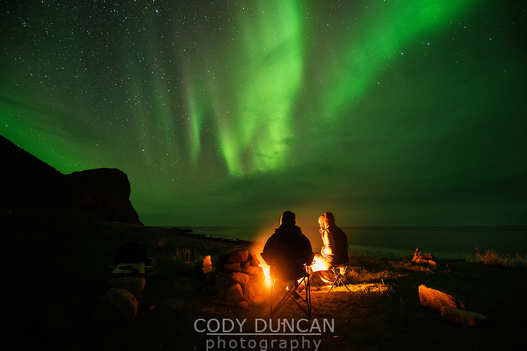 sitting around an campfire with northern lights - aurora borealis in the sky overhead, Unstad, Vestvågøy, Lofoten Islands, Norwya
