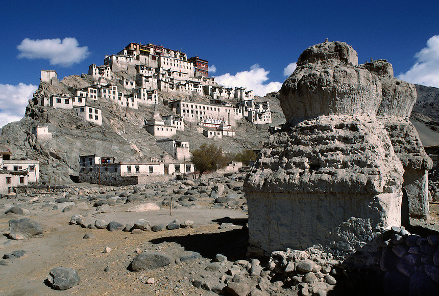 TIKSE GOMPA (monastery), built in the 15th century, rises above BUDDHIST CHORTENS - LADAKH, INDIA.