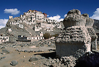 TIKSE GOMPA (monastery), built in the 15th century, rises above BUDDHIST CHORTENS - LADAKH, INDIA.