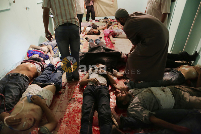Supporters of the Muslim Brotherhood stand next to the bodies of fellow protesters killed in clashes with Republican Guards forces, at a hospital morgue in Cairo, Egypt, 08 July 2013. Clashes between Islamist protesters and the army in Cairo erupted at dawn on 08 July, killing at least 42 and injuring 322 others, according a health official. Fighting broke out when an armed group attempted to storm the Republican Guards club, where the ousted president Mohamed Morsi is thought to be held by the army. The violence amplifies the conflict between the army and supporters of the Muslim Brotherhood group, who vowed to continue demonstrating until he is restored to power. Photo by Wissam Nassar
