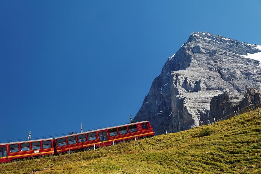 Red rail cars on the Jungfrau railway run below the north face of the Eiger at Kleine Scheidegg, Bernese Oberland, Switzerland