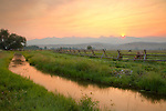 Idaho, East Central, Lemhi County, Salmon. Sunrise over the Beaverhead Mountains of the Bitterroot Range and an irrigation canal and horse pasture in the Salmon River Valley.