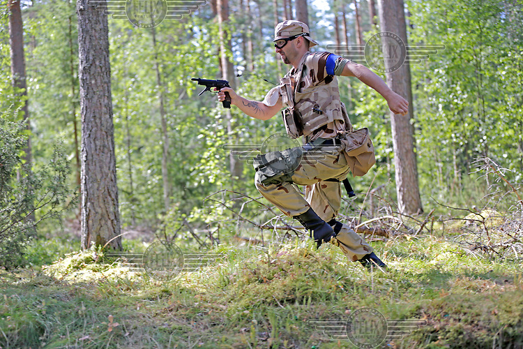 """A player from team SOB rush enemy positions, only to be shot himself.<br /> <br /> Airsoft players fight during the mock war """"Ghost Zone"""". The game attracted around 140 players from all over Norway, and is the biggest such event in the country. Dressed in full military gear, complete with replica weapons, players from the two teams Goyo and SOB fought each other to control territory, drugs and money. The guns, softguns, weigh and feel like real weapons but only shoot little plastc pellets. All players wear protective glasses for their eyes, but the pellets are otherwise not considered dangerous."""